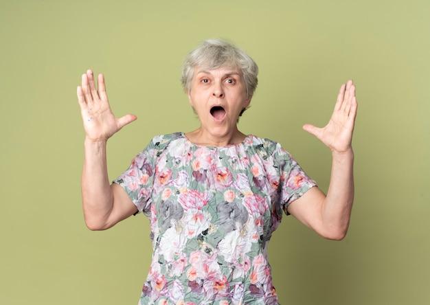 Geërgerd oudere vrouw heft handen op en schreeuwt geïsoleerd op olijfgroene muur