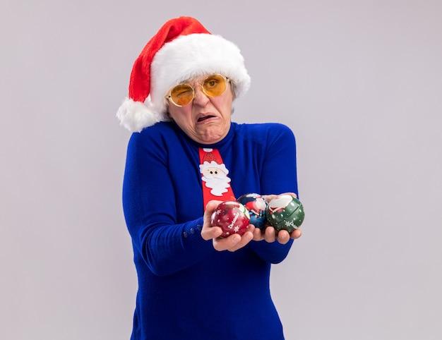 Geërgerd oudere vrouw in zonnebril met kerstmuts en santa stropdas glas bal ornamenten houden