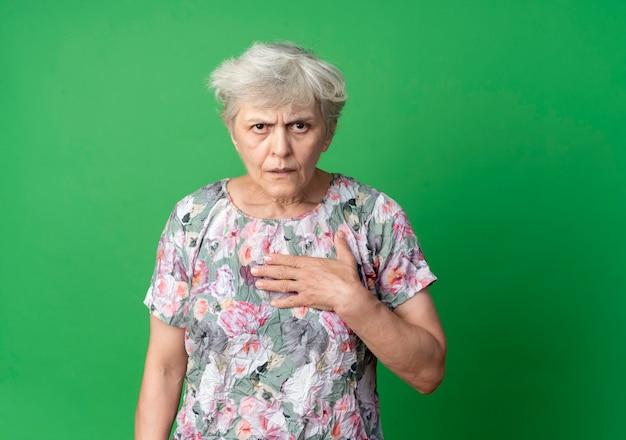 Geërgerd oudere vrouw legt hand op kin en kijkt geïsoleerd op groene muur