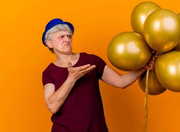 Geërgerd oudere vrouw met feestmuts houdt en wijst naar helium ballonnen geïsoleerd op oranje muur met kopie ruimte