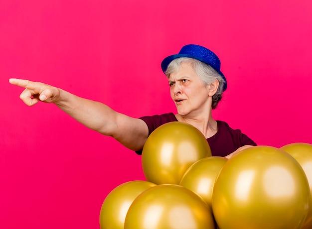 Geërgerd oudere vrouw met feestmuts staat met helium ballonnen kijken en wijzend naar de zijkant op roze