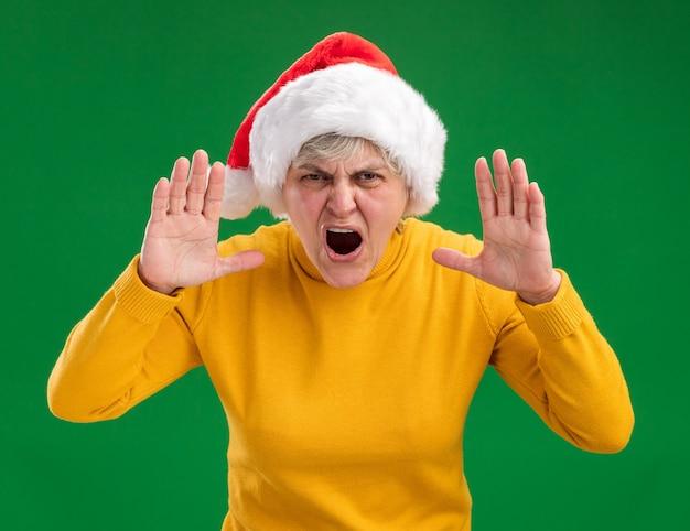 Geërgerd oudere vrouw met kerstmuts schreeuwen tegen iemand kijken naar camera geïsoleerd op paarse achtergrond met kopie ruimte