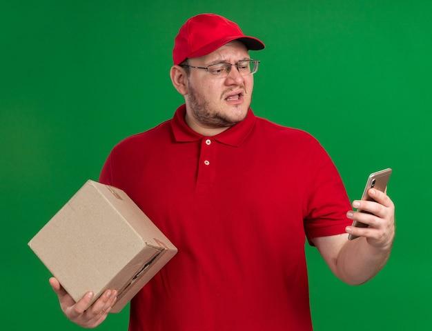 Geërgerd overgewicht jonge bezorger in optische bril met kartonnen doos en kijken naar telefoon geïsoleerd op groene muur met kopieerruimte