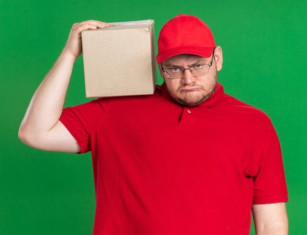 Geërgerd overgewicht jonge bezorger in optische glazen met kartonnen doos op schouder geïsoleerd op groene muur met kopie ruimte