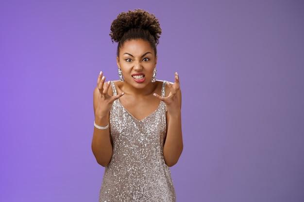 Geërgerd pissig arrogant freak-out afro-amerikaanse vrouw in zilveren jurk vuisten knijpen boos fronsen grimassen woede woedend kijken camera gehinderd schreeuwen woede reageren schandalig gebrek aan respect.