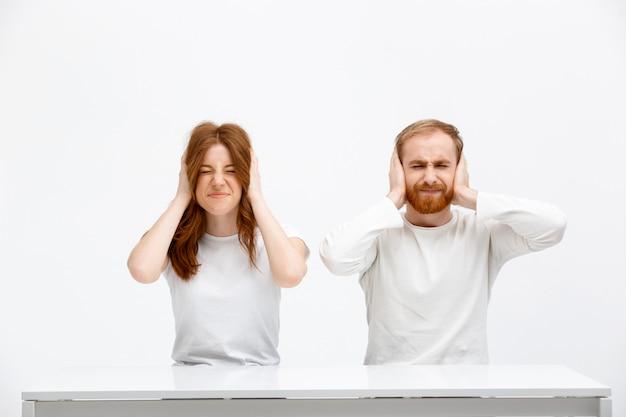 Geërgerd roodharige man en vrouw gesloten oren