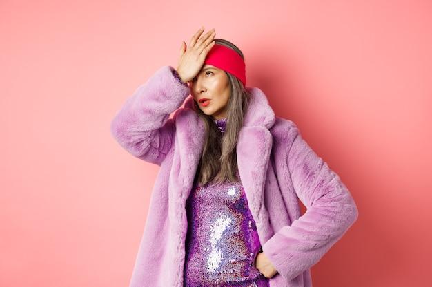 Geërgerd senior vrouw rolt ogen en maakt facepalm van iets kleins, staande in trendy paarse winterjas en glinsterende jurk op roze.