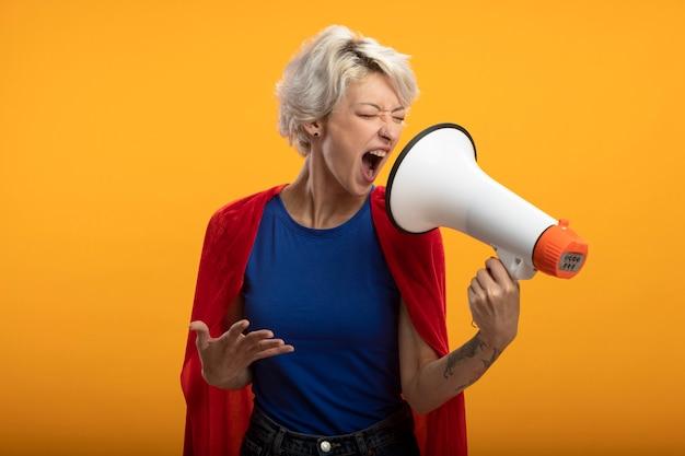 Geërgerd supervrouw met rode cape houdt hand open en roept in luide spreker die op oranje muur wordt geïsoleerd