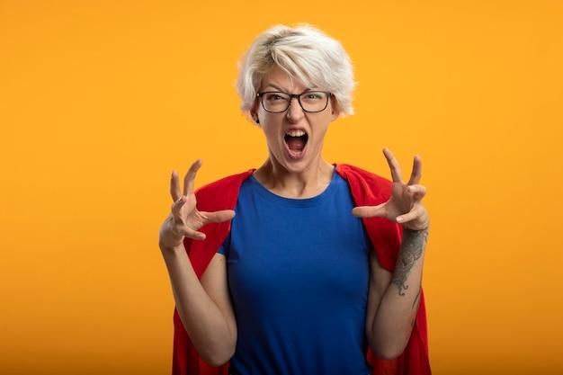 Geërgerd supervrouw met rode cape in optische glazen gebaren tijgerpoten geïsoleerd op oranje muur