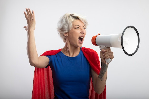 Geërgerd supervrouw met rode cape staat met opgeheven hand en schreeuwt in luide spreker die op witte muur wordt geïsoleerd