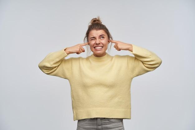 Geërgerd uitziende vrouw, ongelukkig meisje met blond haar in een knot. gele trui dragen. sluit haar oren met de vingers, het is te lovend. kijken naar kopie ruimte, geïsoleerd over witte muur