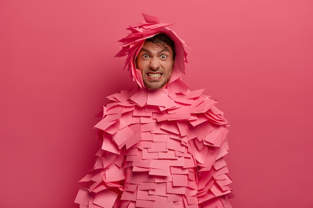 Geërgerd volwassen man klemt zijn tanden, maakt een boze grimas, bedekt met plakbriefjes, heeft een creatief kostuum, klemt zijn tanden op elkaar, geïsoleerd over roze muur, fronst zijn wenkbrauwen. het concept van menselijke gezichtsuitdrukkingen