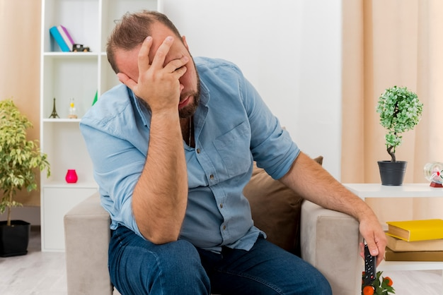 Geërgerd volwassen slavische man zit op fauteuil hand op gezicht houden tv afstandsbediening in de woonkamer