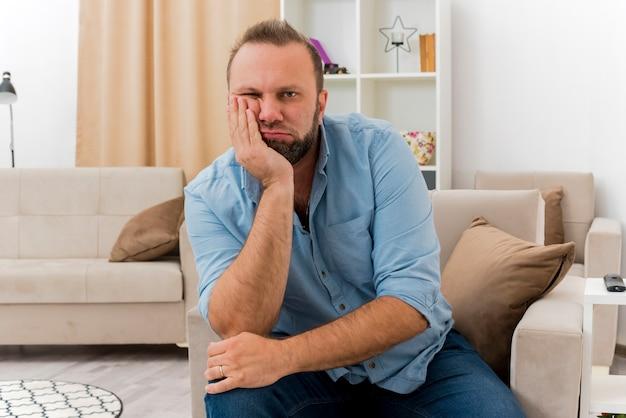 Geërgerd volwassen slavische man zit op fauteuil hand zetten gezicht camera kijken in de woonkamer