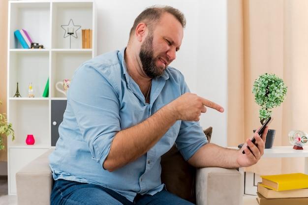 Geërgerd volwassen slavische man zit op fauteuil kijken en wijzend op telefoon in de woonkamer