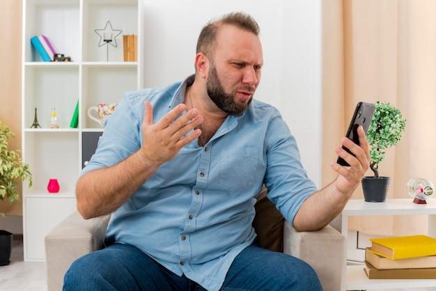 Geërgerd volwassen slavische man zit op fauteuil met opgeheven hand kijken naar telefoon in de woonkamer
