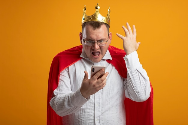Geërgerd volwassen superheld man in rode cape bril en kroon houden en kijken naar mobiele telefoon houden hand in lucht geïsoleerd op oranje muur