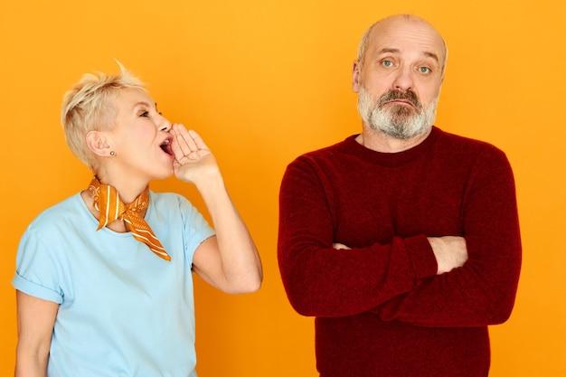 Geërgerd volwassen vrouwtje met kort blond haar dat hand bij haar mond houdt en iets schreeuwt naar echtgenoot die negeert, niet naar haar luistert, de armen over zijn borst gevouwen houdt. relaties concept
