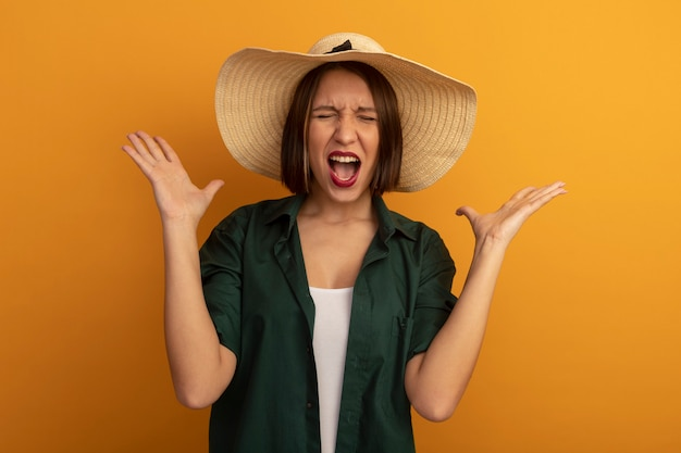 Geërgerd vrij blanke vrouw met strandhoed staat met opgeheven handen op sinaasappel