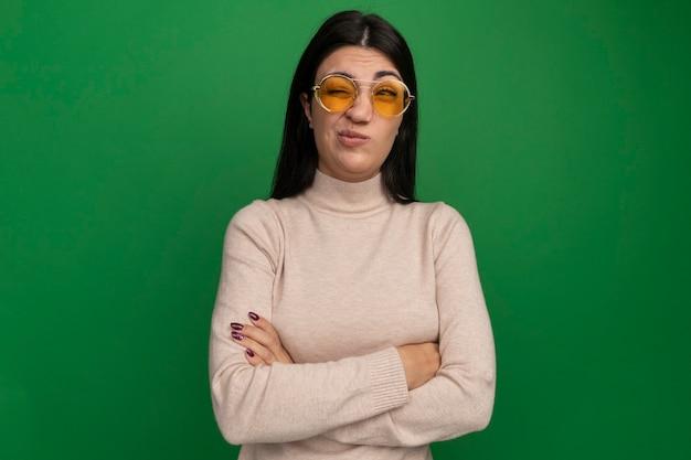 Geërgerd vrij brunette kaukasisch meisje in zonnebril staat met gekruiste armen kant op groen kijken