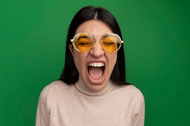 Geërgerd vrij donkerbruin kaukasisch meisje in zonglazen schreeuwt op groen