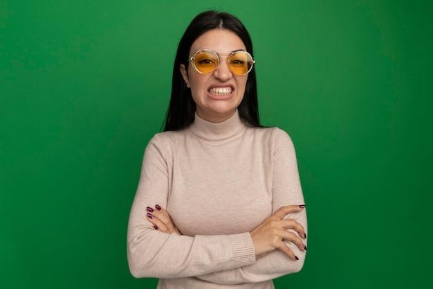 Geërgerd vrij donkerbruin kaukasisch meisje in zonnebril staat met gekruiste armen op groen