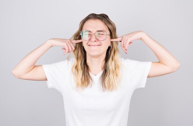 Geërgerd vrouw steken plug vingers in oren niet luisteren naar hard geluid geluid geïsoleerd op witte lege studio achtergrond.