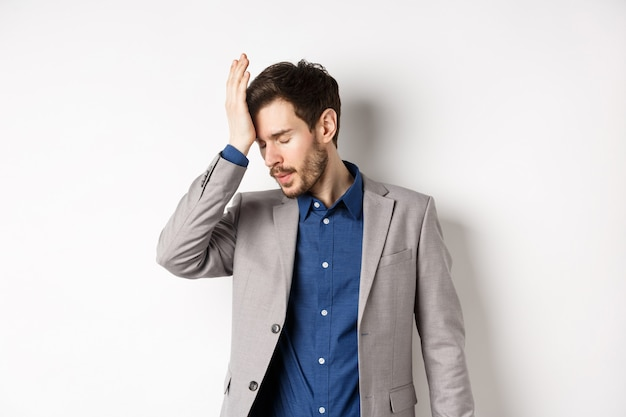 Geërgerd zakenman in pak facepalm met gesloten ogen, gehinderd door dom iemand Premium Foto