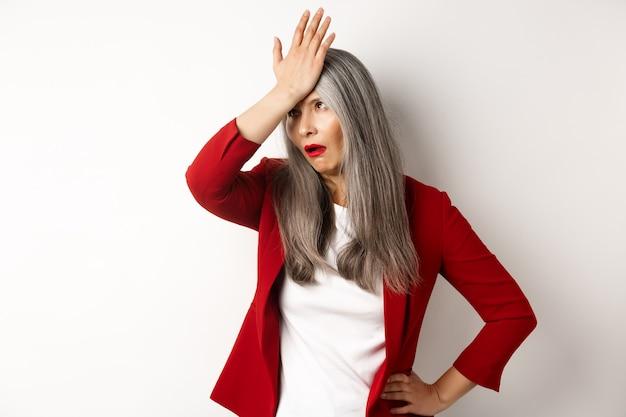 Geërgerde aziatische kantoordame in rode blazer met rologen en facepalm, staande gehinderd en geïrriteerd over witte muur.