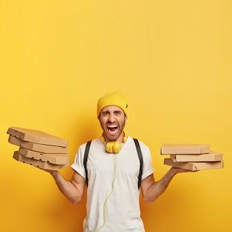 Geërgerde bezorger draagt veel kartonnen dozen met pizza, roept geïrriteerd, heeft veel werk tegelijk, veel bestellingen van klanten