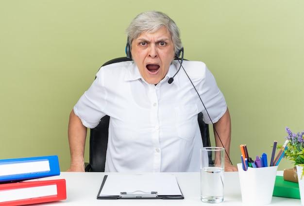 Geërgerde blanke vrouwelijke callcenter-operator op koptelefoon die aan het bureau zit met kantoorhulpmiddelen die tegen iemand schreeuwen