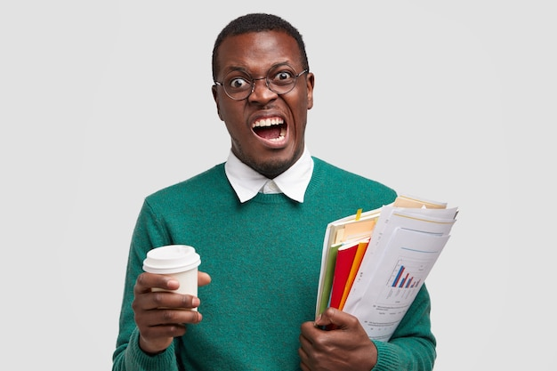 Geërgerde donkere man fronst gezicht, wil geen economie, markt, geld en belasting studeren, beleggingsadviseur zijn, analyseert jaarverslag van het bedrijf