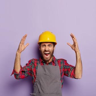 Geërgerde emotionele werkman draagt gele beschermende constructiehelm, geruit overhemd en schort, heeft veel werk te doen, schreeuwt van stress en paniek, heft emotioneel de armen op