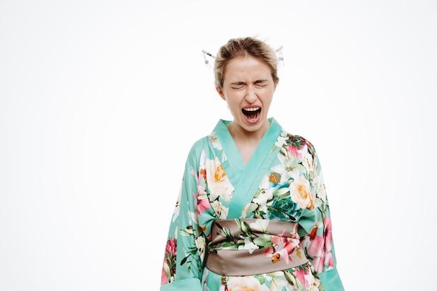 Geërgerde en boze vrouw in traditionele japanse kimono die schreeuwt en schreeuwt en wild wordt op wit