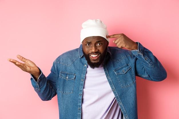 Geërgerde en pissige afro-amerikaanse man die met de vinger naar het hoofd wijst, iemand dom uitscheldt, starend naar de camera, roze achtergrond