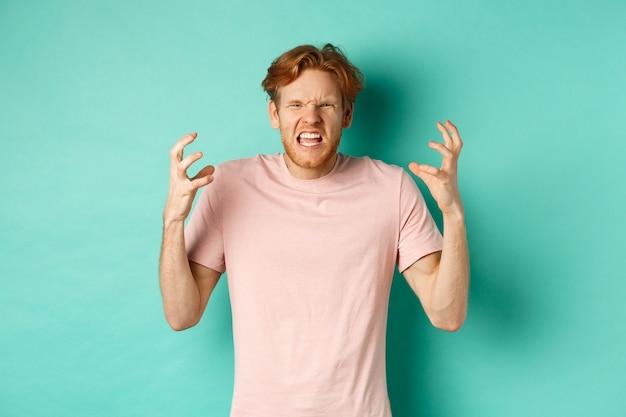 Geërgerde en pissige roodharige man die boos kijkt, schreeuwt en grimast, agressief handen schudt, woedend staat tegen muntachtergrond.