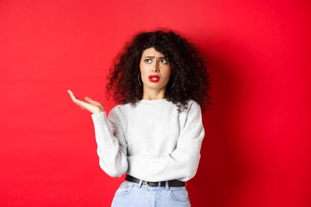 Geërgerde en verbaasde jonge vrouw met krullend haar, handen opstekend en opzij kijkend, kan iets vreemds niet begrijpen, staande op een rode achtergrond.