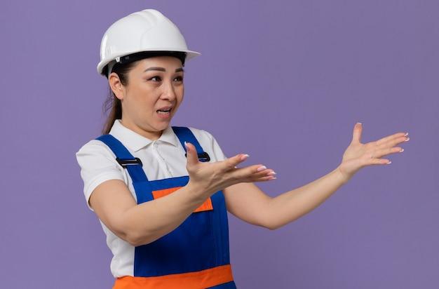 Geërgerde jonge aziatische bouwvrouw met witte veiligheidshelm die de handen open houdt en naar de zijkant kijkt