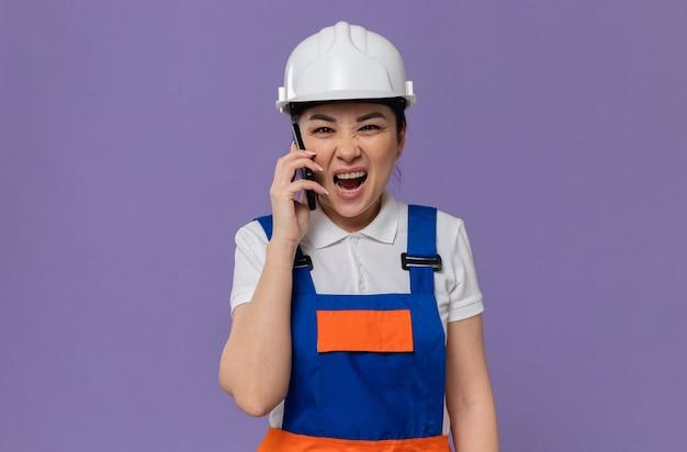 Geërgerde jonge aziatische bouwvrouw met witte veiligheidshelm die tegen iemand aan de telefoon schreeuwt
