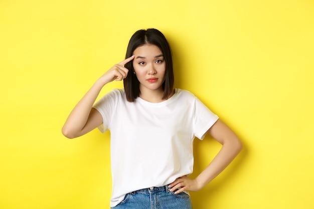 Geërgerde jonge aziatische vrouw die stom iemand uitscheldt, vinger naar het hoofd richt, vraagt of je gek bent, staande over gele achtergrond.