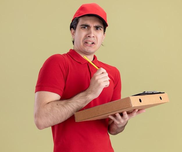 Geërgerde jonge bezorger in rood uniform en pet met pizzapakket klembord en potlood kijkend naar voorkant geïsoleerd op olijfgroene muur
