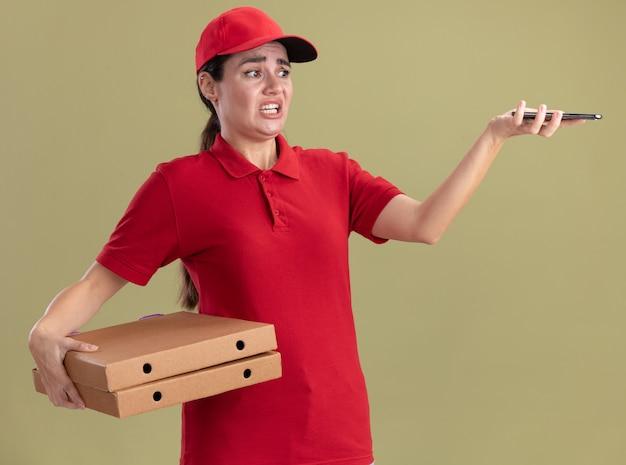 Geërgerde jonge bezorger in uniform en pet met pizzapakketten en mobiele telefoon die naar de telefoon kijkt