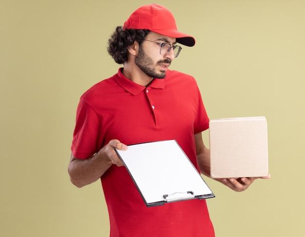 Geërgerde jonge blanke bezorger in rood uniform en pet met een bril met cardbox en klembord kijkend naar cardbox