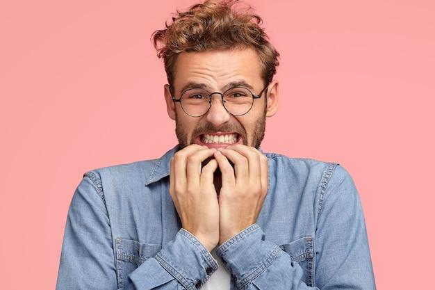 Geërgerde jonge blanke man klemt tanden en kijkt met een ontevreden uitdrukking, bijt op de nagels, kijkt wanhopig, voelt afkeer, draagt een spijkerblouse, staat tegen een roze muur. oh nee!