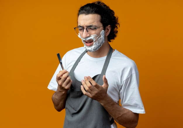 Geërgerde jonge blanke mannelijke kapper met een bril en een golvende haarband in uniform vasthouden en kijken naar een scheermes met scheerschuim op zijn gezicht, hand in de lucht houdend