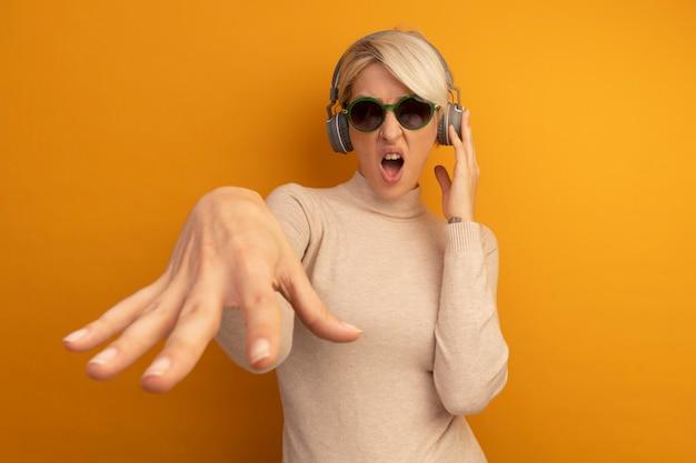Geërgerde jonge blonde vrouw die een zonnebril en hoofdtelefoon draagt die een hoofdtelefoon aanraakt