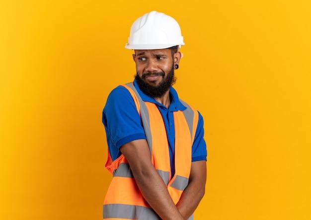 Geërgerde jonge bouwer man in uniform met veiligheidshelm kijkend naar kant geïsoleerd op oranje muur met kopieerruimte