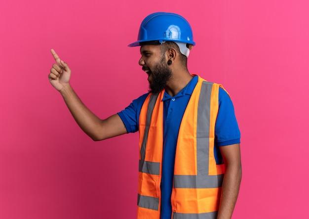Geërgerde jonge bouwman in uniform met veiligheidshelm schreeuwend tegen iemand die naar kant kijkt geïsoleerd op roze muur met kopieerruimte