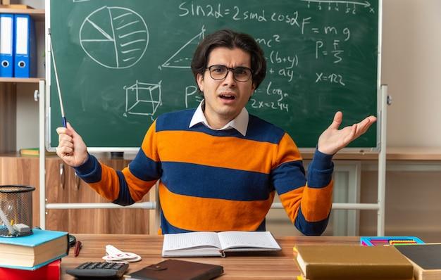 Geërgerde jonge kaukasische meetkundeleraar met een bril die aan het bureau zit met schoolbenodigdheden in de klas met een aanwijzer die naar de voorkant kijkt en een lege hand toont