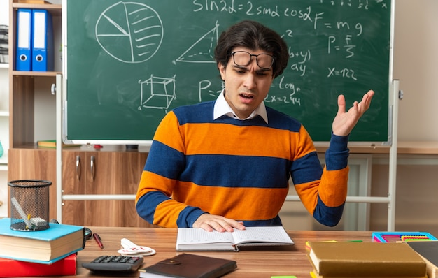 Geërgerde jonge kaukasische meetkundeleraar met een bril op het voorhoofd zittend aan een bureau met schoolbenodigdheden in de klas die de hand op een open boek houdt en het leest met lege hand